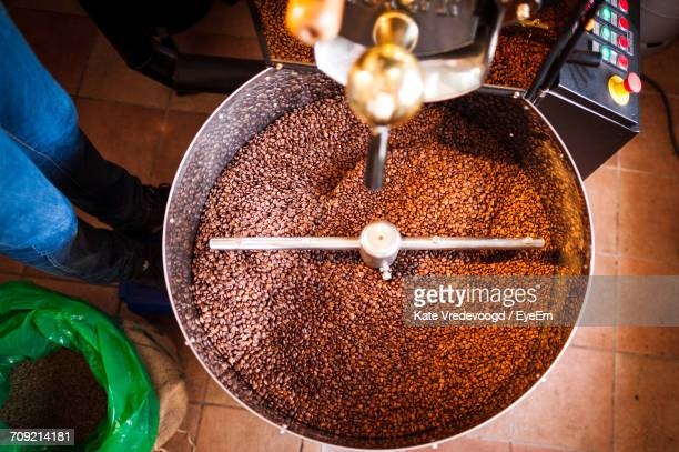 Low Section Of Worker Standing By Coffee Grinder In Cafe