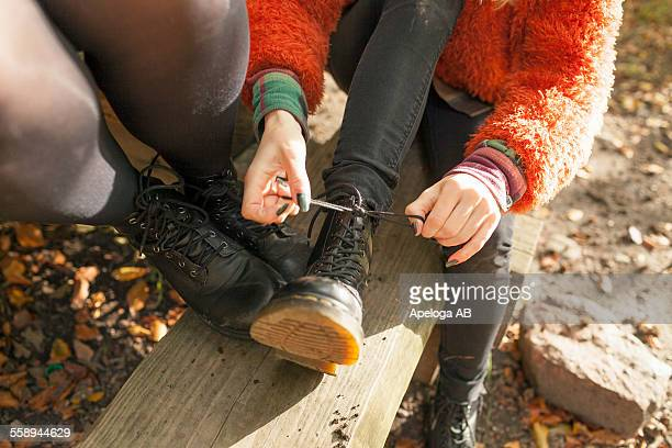 Low section of young woman tying shoelace by female friend in forest