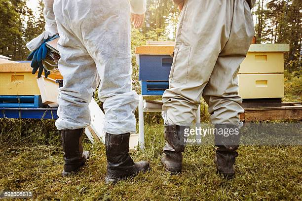 Low section rear view of beekeepers standing on field