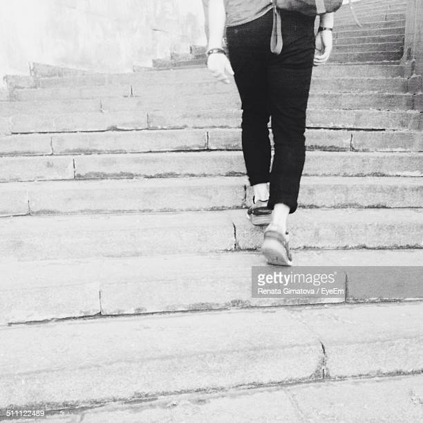 Low section rear view woman climbing steps outdoors