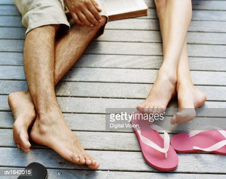 Low Section Shot of Couple Lying on Decking