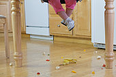 Low section view of a baby girl with spilled food on the floor