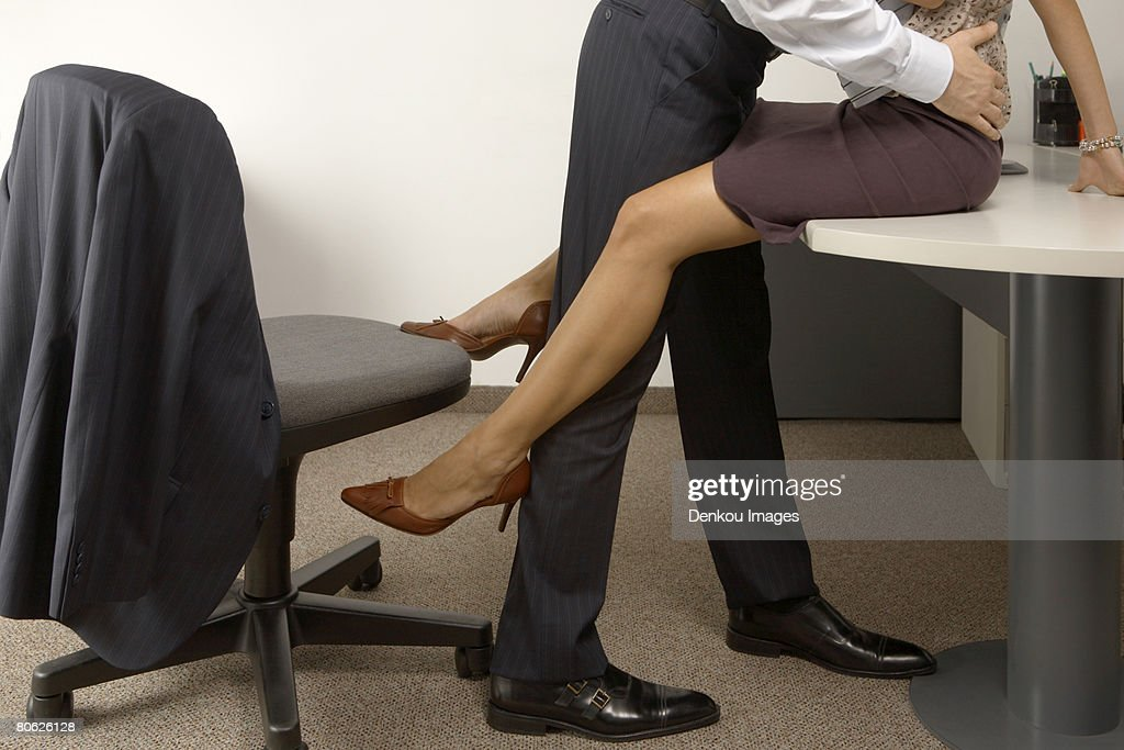 Low section view of a businessman and a businesswoman flirting in an office : Foto de stock