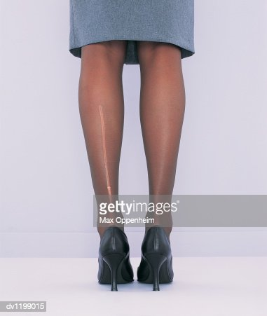 Low Section View of a Businesswoman's Torn Tights : Stock Photo
