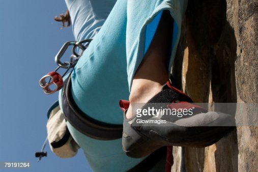 Low section view of a female climber rock climbing : Foto de stock
