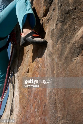 Low section view of a female climber scaling a rock face : Foto de stock