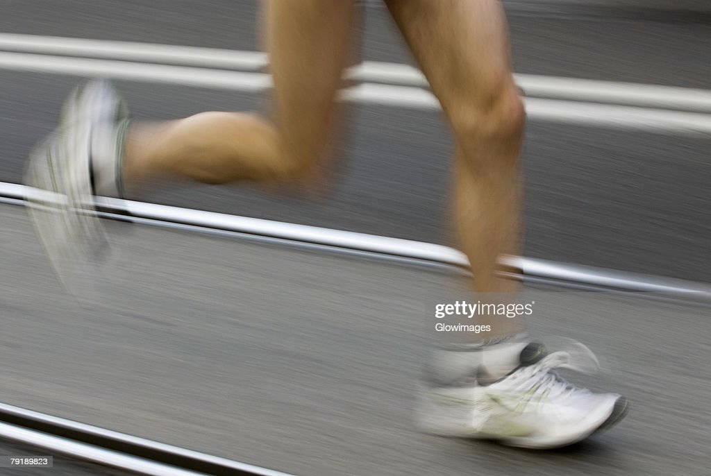 Low section view of a male athlete running on a running track : Foto de stock