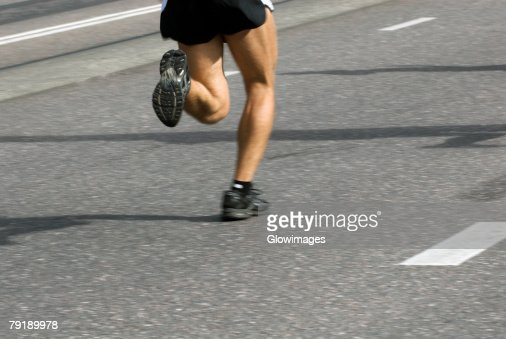 Low section view of a male athlete running on a running track : Stock Photo