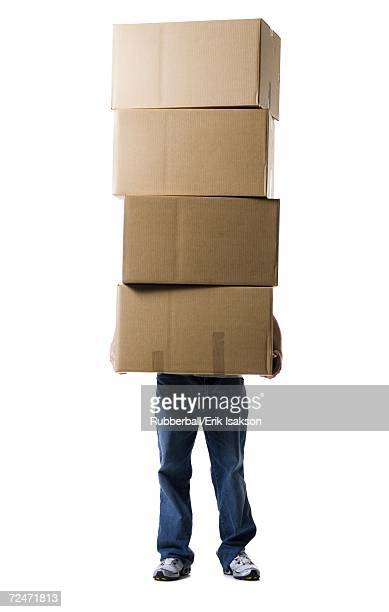 Low section view of a man holding a stack of cardboard boxes