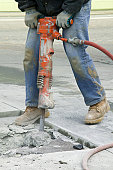 Low section view of a man operating a jackhammer on the road