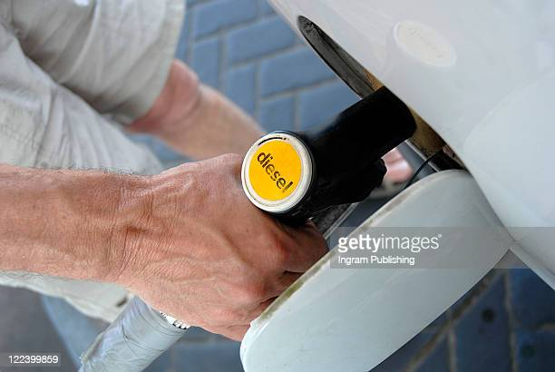 Low section view of a man refueling a car
