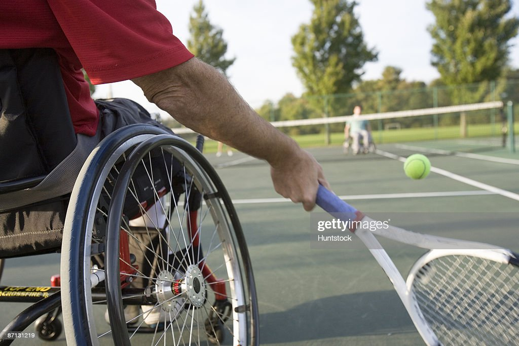 Low section view of a man sitting in a wheelchair and playing tennis.