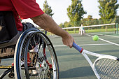Low section view of a disabled man sitting in a wheelchair and playing tennis