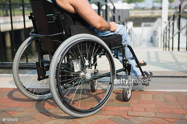 Low section view of a man sitting in a wheelchair