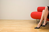 Low section view of a mid adult woman sitting on a couch
