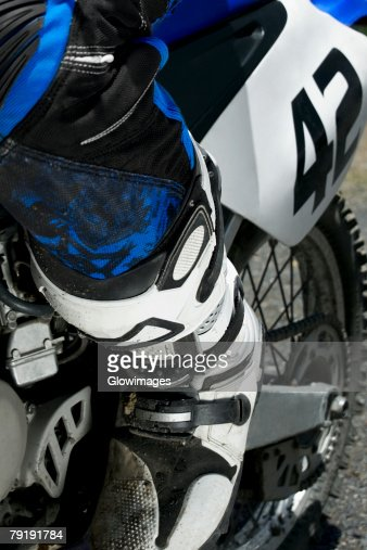 Low section view of a motocross rider riding a motorcycle : Stock Photo