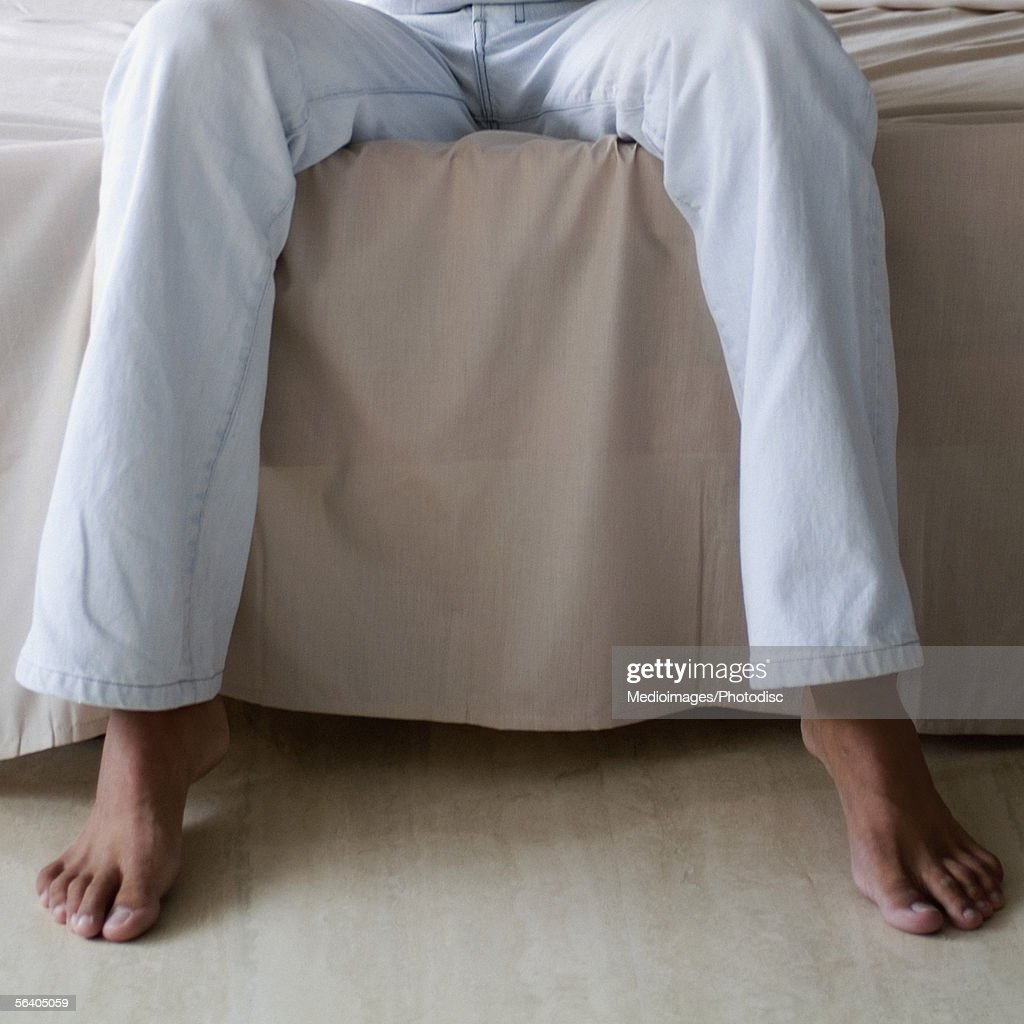 Low section view of a person sitting on a bed