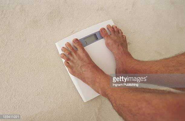 Low section view of a person standing on a weighing scale