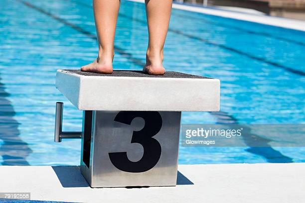 Low section view of a person standing on the diving platform