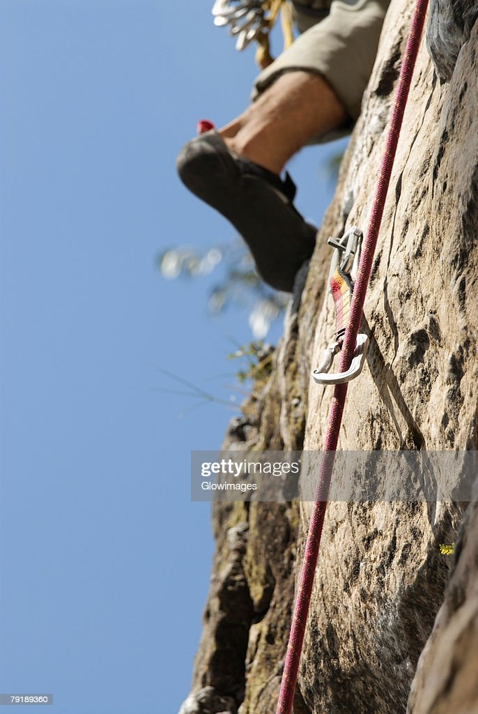 Low section view of a rock climber scaling a rock face : Stock Photo