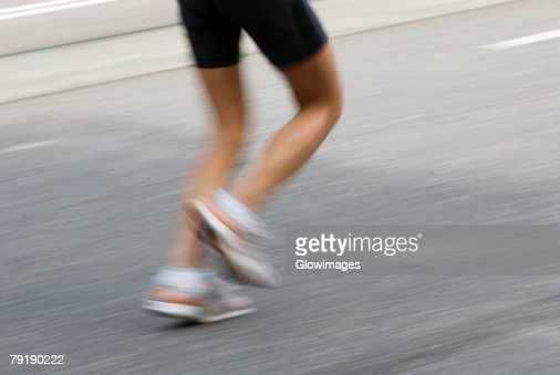 Low section view of a track runner running : Foto de stock