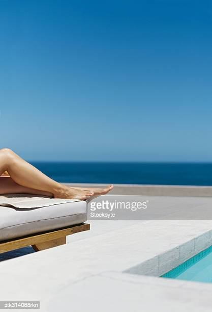 low section view of a woman lying on a lounge chair