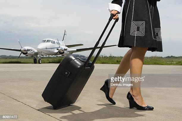 Low section view of a woman pulling her luggage
