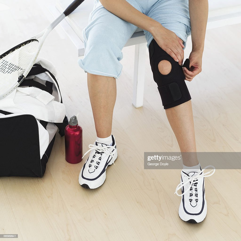 low section view of a woman putting on a knee pad