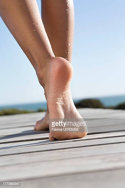 Low section view of a woman walking on boardwalk on the beach