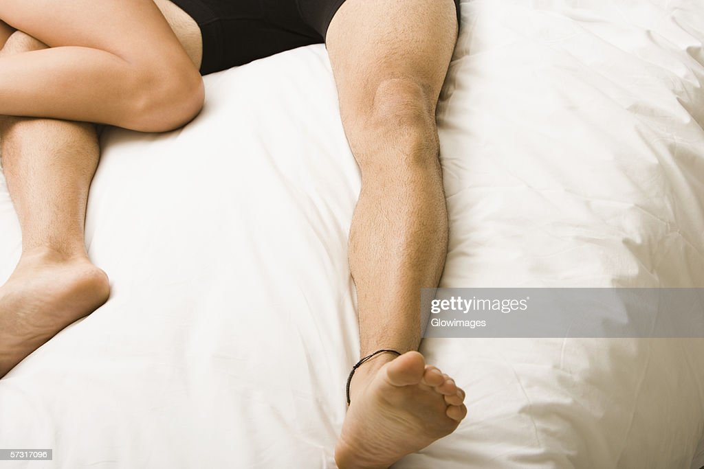Low section view of a young couple lying on the bed : Stock Photo