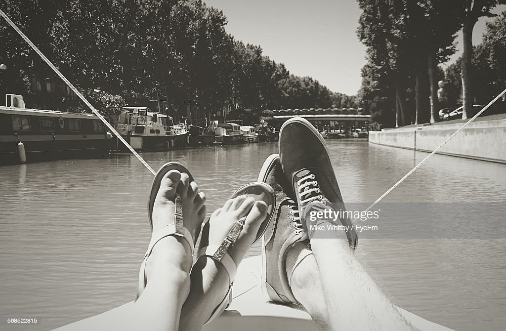 Low Section View Of Couple Relaxing On Boat