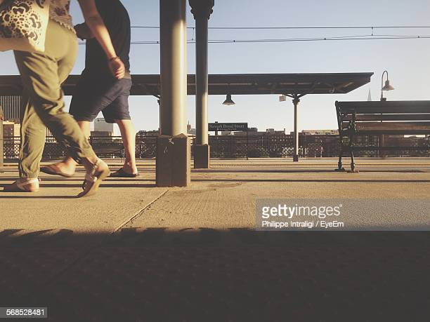 Low Section View Of Couple Walking At Railroad Platform