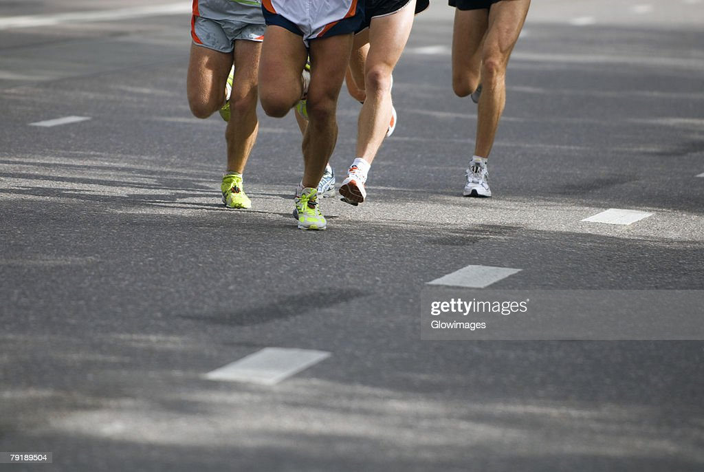 Low section view of male athletes running on a road : Foto de stock