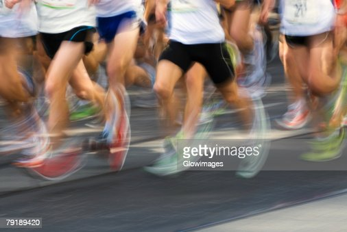 Low section view of male athletes running on a running track : Foto de stock