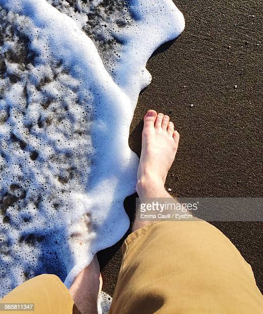 Low Section View Of Man Walking On Beach