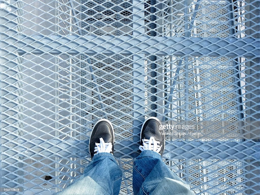 Low Section View Of Person Standing On Metal Grate