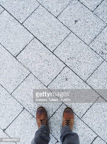 Low Section View Of Person Standing On Sidewalk