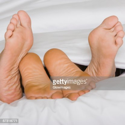 Low section view of the feet of two people on a bed : Stock Photo