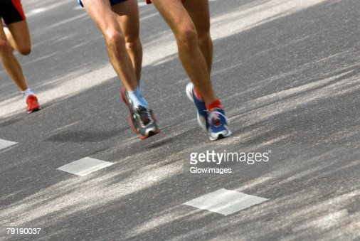 Low section view of three track runners running : Stock Photo