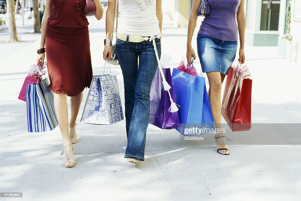 Low section view of three women walking and holding shopping bags : Foto de stock
