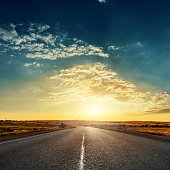 low sun in dramatic sky over asphalt road