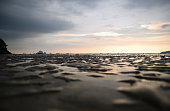 The beach as the water retreats, leaving small puddles and bumpy texture, during sunset