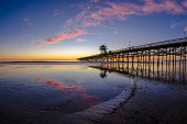 Low tide at San Clemente Pier with pink clouds