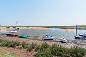 Small boats are beached either on the beach or small sandbanks at low tide in the estuary at Wells-next-the-Sea