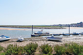 Rowing boats and small motor boats are tied up alongside a small jetty  at low tide at Wells-next-the-Sea