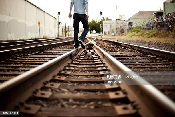 Low view of a male figure walking down some train tracks