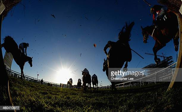 A low winter sun shines towards the horses and riders as they jump a Steeple Chase jump at Cheltenham Racecourse on December 13 2014 in Cheltenham...