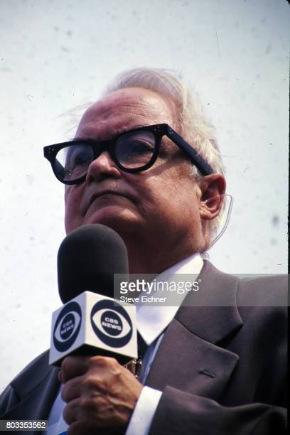 Lowangle closeup of American actor Calvert DeForest in costume as charcter Larry 'Bud' Melman as he holds a CBS News microphone at the Woodstock '94...