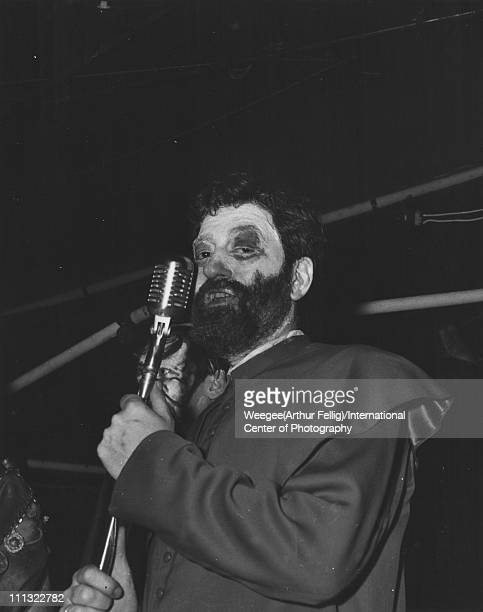 Lowangle portrait of a costumed man with a heavily madeup face as he stands at a mircophone New York New York mid 1950s Photo by Weegee/International...