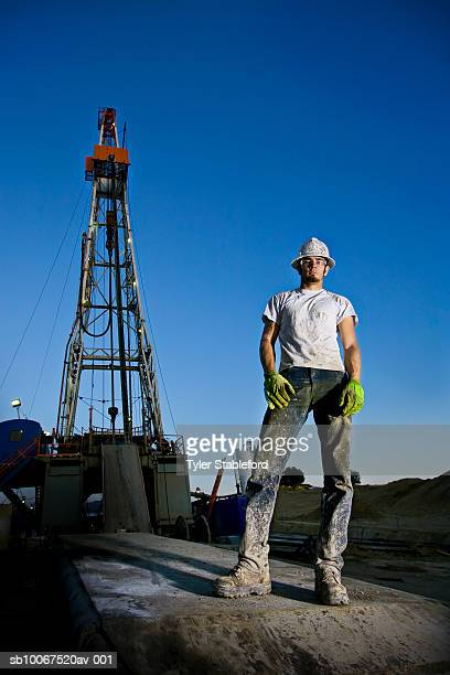Low-angle portrait of oil worker on drilling platform
